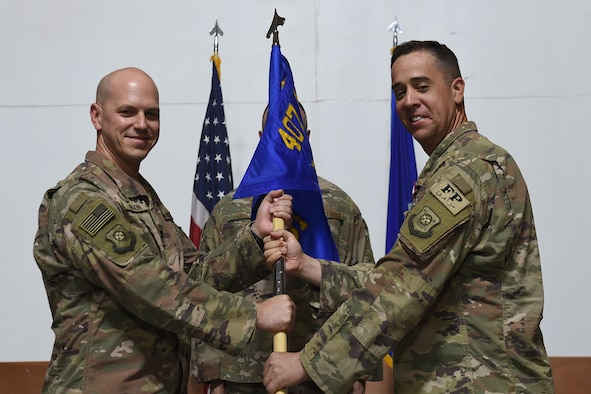 Two Airmen hold on to squadron flag