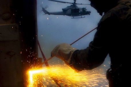 A reconnaissance Marine with the 31st Marine Expeditionary Unit's Force Reconnaissance Platoon uses an exothermic torch to cut through a steel obstacle during a combined sea and airborne Visit, Board, Search and Seizure exercise as part of Realistic Urban Training Exercise, off the coast of Okinawa, Japan, July 26, 2017.