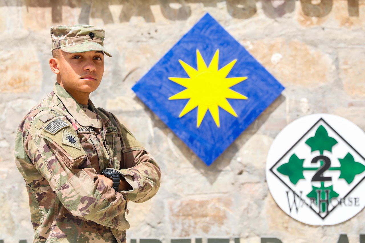 A soldier stands in front of the 40th Infantry Division logo.