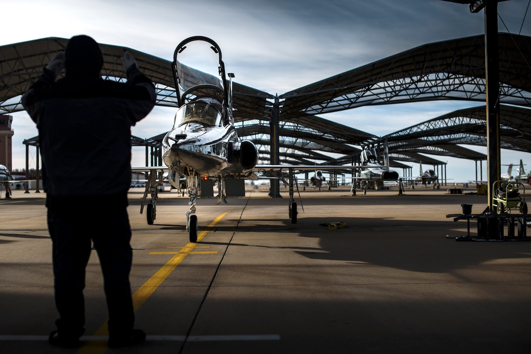 An L3 Maintenance contractor directs a T-38C Talon to its parking spot Feb. 1, 2018, at Vance Air Force Base, Oklahoma. The T-38 is a two-seat, twinjet supersonic jet trainer. It was the world's first supersonic trainer and is also the most produced. (U.S. Air Force photo by Senior Airman Corey Pettis)