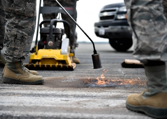 Airmen from Spangdahlem Air Base's 52nd Civil Engineer Squadron use a torch to make asphalt malleable while Staff Sgt. David Springsteen, a pavements and construction helper from the 910th Civil Engineer Squadron, prepares a compactor on the Spangdahlem flightline, July 12, 2018.