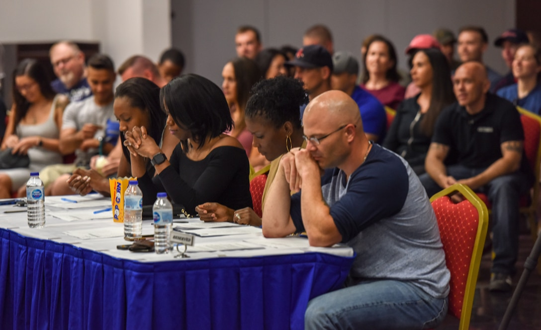 Judges watch contestants as they perform their poses