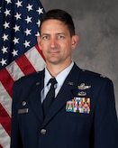 Dark haired white male Air Force colonel in blues in front of  red, white and blue American flag and grey background.