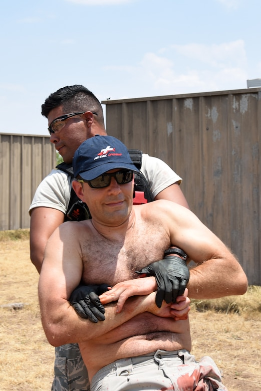 U.S. Air Force Airman 1st Class Luis Vazquez, 17th Security Forces Squadron Emergency Services Team member, pulls Tactical Medics Group Actor Leonid Kalmanovich during a Tactical Combat Casualty Care Course near building 3070 on Goodfellow Air Force Base, Texas, July 27, 2018. Several security forces members took the course to learn how to provide first aid as first responders during a mass casualty incident. (U.S. Air Force photo by Staff Sgt. Joshua Edwards/Released)