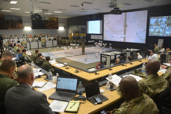Military leaders gather in a large room.