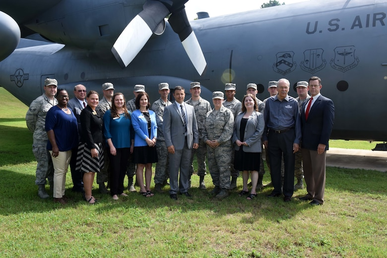 A group of individuals, both in uniform and in civilian business attire, stand in the grass in front of a large grey C-130H aircraft for a group photo.