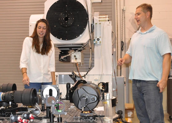 IMAGE: DAHLGREN, Va. (July 10, 2018) - Sarah Wessel and her mentor, Naval Surface Warfare Center Dahlgren Division engineer Matt Henning, examine the Advanced Beam Control Locating and Engaging - Enhanced Tracking System (ABLE-ETS) gimbal. The ABLE ETS Gimbal is part of a pointing and image tracking system. Last summer, Wessel converted the gimbal's pointing controller Simulink code into C++ code. ABLE-ETS is a Joint Technology Office funded test bed for maturing directed energy and high-energy laser technologies, including tracking, sensors, and lasers.   Wessel is interning at Dahlgren through the STEM (science, technology, engineering and mathematics) Student Employment Program (SSEP). The program provides direct hire authority for undergraduate and graduate degree seeking students enrolled in STEM majors. The program was established to provide interns with exposure to public service, enhance educational experience, and possibly provide financial aid to support educational goals. Additionally, this program will provide a streamlined and accelerated hiring process to compete successfully with private industry for high-quality scientific, technical, engineering, or mathematics students for filling scientific and engineering positions.