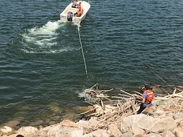 Crews at the Garrison Dam in North Dakota are removing logs and debris from the approach channel and embankment near the spillway.