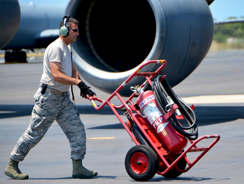 Tech. Sgt. Timothy Hardy, 507th Aircraft Maintenance Squadron crew chief from Tinker Air Force Base, Oklahoma, rolls a fire extinguisher into place near a 97th Air Mobility Wing KC-135 Stratotanker from Altus Air Force Base, Oklahoma, during the Rim of the Pacific (RIMPAC) exercise July 16. Twenty-five nations, 46 ships, five submarines, and about 200 aircraft and 25,000 personnel are participating in RIMPAC from June 27 to Aug. 2 in and around the Hawaiian Islands and Southern California. The world's largest international maritime exercise, RIMPAC provides a unique training opportunity while fostering and sustaining cooperative relationships among participants critical to ensuring the safety of sea lanes and security of the world's oceans. RIMPAC 2018 is the 26th exercise in the series that began in 1971. (U.S. Air Force photo by Tech. Sgt. Samantha Mathison)