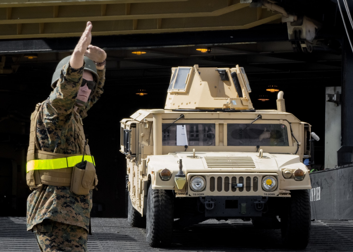 Cpl. Bradley Graczyk, combat engineer with Combat Logistics Regiment 45 directs a Humvee offloading from USNS Sgt. William R. Button during a maritime prepositioning force offload at the port of Klaipeda, Lithuania, May 23, 2018.