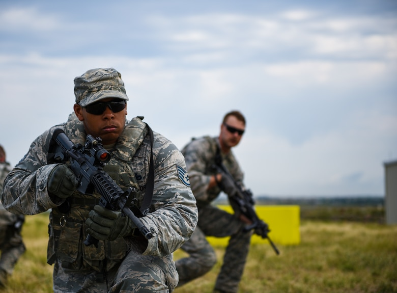 Staff Sgt. Phillip Edwards and Airman 1st Class Austin Cherry, 460th Security Forces Squadron defenders, conduct tactical movements during a field exercise in preparation for the Defenders Challenge July 27, 2018, on Buckley Air Force Base, Colorado. Select Air Force Space Command defenders will compete against one another at Peterson Air Force Base, Colorado, and then winners will compete at Camp Bullis, Texas, for the final challenge.  (U.S. Air Force photo by Airman 1st Class Michael D. Mathews)