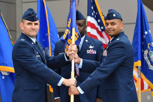 Col. Hewett Wells, commander of the 50th Network Operations Group, hands the 22nd Space Operations Squadron guidon to Maj. Sanil Amin new commander of the 22nd SOPS during a change of command ceremony at Schriever Air Force Base, Colorado, July 27, 2018.  Maj. Amin assumed command from Lt. Col. Lewis Sorvillo. (U.S. Air Force Photo/Dennis Rogers)
