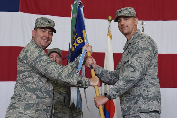 Col. James T. Vinson accepts the guideon during the 51st Maintenance Group Change of Command ceremony at Osan Air Base, Republic of Korea July 20, 2018. Vinson was commissioned through the Reserve Officer Training Corps program in June of 1996. A career aircraft maintenance officer, he served in a variety of positions at Wing, Major Command, Headquarters Air Force, and Office of the Secretary of Defense levels. Vinson's previous assignment was Military Deputy, Office of the Deputy Assistant Secretary of Defense for Supply Chain Integration in Washington D.C.