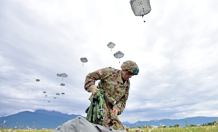A U.S. Army Paratrooper, assigned to the 173rd Brigade Support Battalion, 173rd Airborne Brigade, secures his equipment after exiting a U.S. Air Force 86th Air Wing C-130 Hercules aircraft, during airborne operation at Juliet Drop Zone in Pordenone, Italy May 22, 2018.
