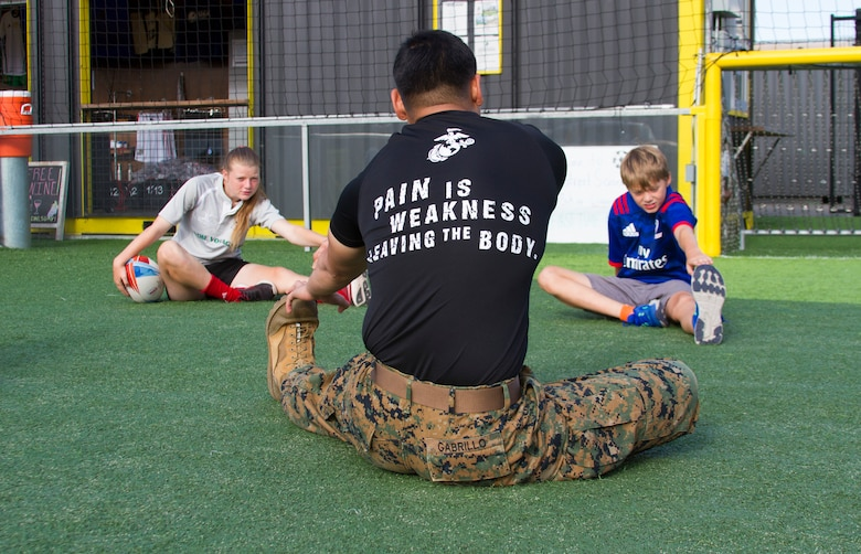 Sgt. Louigene Gabrillo, a recruiter at Recruiting Substation San Mateo, California, conducts a wake up and workout exercise with 14-year-old Skylar Jordan and 11-year-old Zach Cuddy, both from Whitman, Massachusetts, before the second day of the Rugby World Cup Sevens in San Francisco, California, July 21, 2018. This year, the Marine Corps attended the Rugby World Cup Sevens as part of its partnership with USA Rugby. Rugby players tend to share the fighting spirit embodied in Marines and by partnering with USA Rugby, the national governing body for the sport in America, the Marine Corps will reach a broad cross-section of high school and collegiate-aged rugby players as well as an ever-growing influencer network of coaches, referees, rugby alumni and parents.