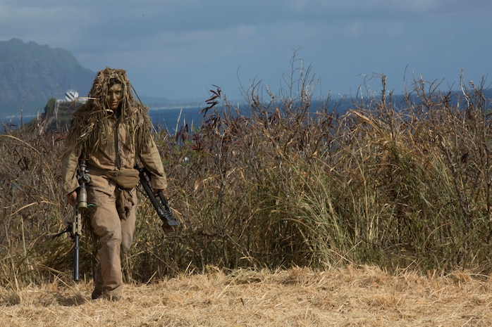 A U.S. Marine Corps scout sniper with 1st Battalion, 3rd Marine Regiment, reveals himself during the amphibious landing demonstration as part of Rim of the Pacific exercise on Marine Corps Base Hawaii July 29, 2018. RIMPAC provides high-value training for task organized, highly capable Marine Air-Ground Task Force and enhances the critical crisis response capability of U.S. Marines in the Pacific. Twenty-Five nations, 46 ships, five submarines, about 200 aircraft, and 25,000 personnel are participating in RIMPAC from June 27 to Aug. 2 in and around the Hawaiian Islands and Southern California.