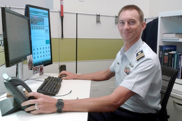 A Coast Guard officer sits at a computer terminal.