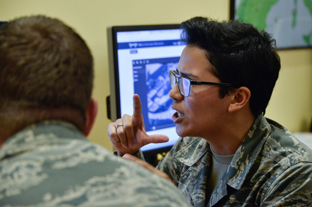 Airman 1st Class Sandra, 7th Intelligence Squadron, explains the how Project Maven works at a booth during the 70th Intelligence, Surveillance and Reconnaissance Wing's 2018 Innovation Summit July 24, 2018 at College Park, Maryland. This was the first summit which helped bring together more than 100 Airmen from across the wing to create a culture of innovation. (U.S. Air Force photo by Staff Sgt. Alexandre Montes)