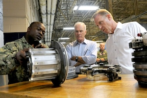 Navy Petty Officer 2nd Class Karil Courtenay, an aviation structural mechanic assigned to Fleet Readiness Center Mid-Atlantic Oceana in Virginia Beach, Va., discusses a hydraulic system part with Deputy Defense Secretary Patrick M. Shanahan, right, and Navy Secretary Richard V. Spencer, during their visit to the center, July 25, 2018. DoD photo by Lisa Ferdinando