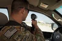 Military Police Investigator Joshua Higgins, 156th Military Police Law and Order Detachment, West Virginia Army National Guard, monitors the speed of traffic on Bagram Airfield, Afghanistan, July 28, 2018. Members of the 156th Military Police Law and Order Det. are deployed to both Bagram and Kandahar Airfields where they perform law and order operations for both installations. (U.S. Air Force photo by Tech. Sgt. Eugene Crist)