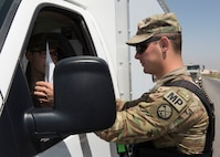 Military Police Investigator Joshua Higgins, 156th Military Police Law and Order Detachment, West Virginia Army National Guard, performs vehicle registration and driver's documentation as part of a random anti-terrorism measures on Bagram Airfield, Afghanistan, July 28, 2018. Members of the 156th Military Police Law and Order Det. are deployed to both Bagram and Kandahar Airfields where they perform law and order operations for both installations. (U.S. Air Force photo by Tech. Sgt. Eugene Crist)