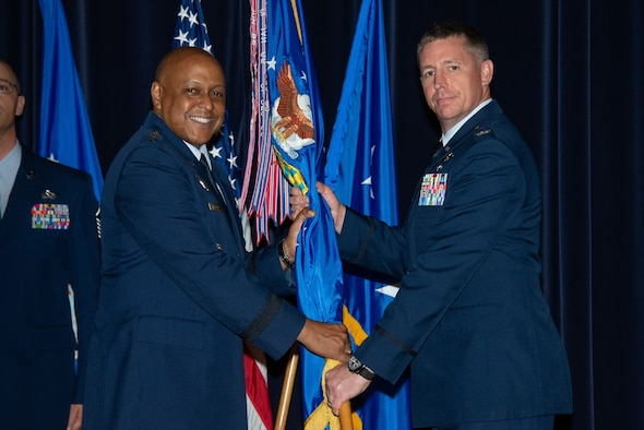 Maxwell AFB, Ala. - Lieutenant General Anthony Cotton, commander and president of Air University (left), presents the Air Command and Staff College guidon to Col. Evan Pettus during a change of command ceremony, July 27, 2018. Air Command and Staff College is the in-residence and distance learning professional military education college of midcareer officers and civilians, focused on the development of air-minded joint leaders.(US Air Force photo by Melanie Rodgers Cox)