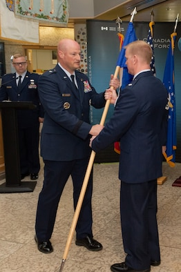 NORAD Deputy Commander Canadian region, Brigadier General Christopher Ireland receives the flag from outgoing Detachment 1 Commander, Lieutenant Colonel Ethan McKenna who relinquishes command during the Det 1, First Airforce change of command ceremony on June 18th, 2018 at 1 CAD, Winnipeg.  Photo by: Cpl Bryce Cooper, 17 Wing Imaging