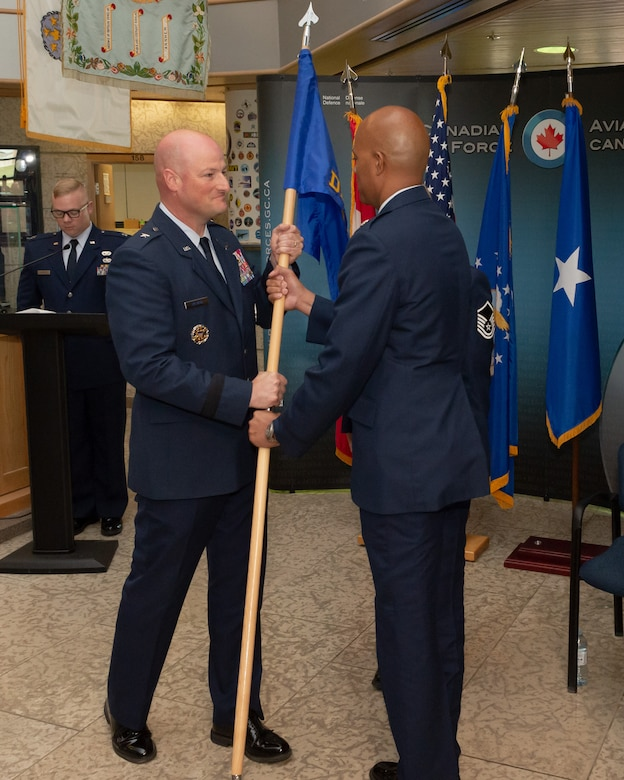 NORAD Deputy Commander Canadian region, Brigadier General Christopher Ireland passes the flag to incoming Detachment 1 Commander, Lieutenant Colonel Brian Hardeman who assumes command during the Det 1, First Airforce change of command ceremony on June 18th, 2018 at 1 CAD, Winnipeg.  Photo by: Cpl Bryce Cooper, 17 Wing Imaging