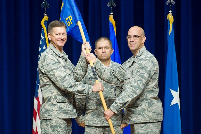 Brig. Gen. Wayne Monteith, commander of the 45th Space Wing, presents Col. Steven Lang, commander of the 45th Operations Group, with the 45th OG guidon, July 31, 2018 at Patrick Air Force Base, Fla. The 45th Launch Group inactivated and combined their launch mission and personnel with the 45th OG. (U.S. Air Force photo by Phillip Sunkel)