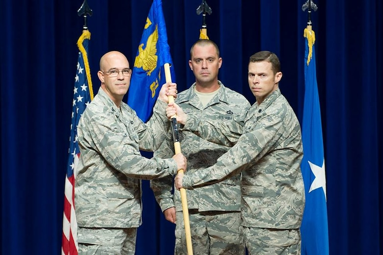 Col. Steven Lang, commander of the 45th Operations Group, presents Lt. Col. Gregory Vice, commander of the 45th Range Squadron, the 45th RANS guidon, July 31, 2018, at Patrick Air Force Base, Fla. The 45th Operations Support Squadron and 1st Range Operations Squadron inactivated and merged its mission and personnel together, now a single squadron, the 45th RANS. (U.S. Air Force photo by Phillip Sunkel)