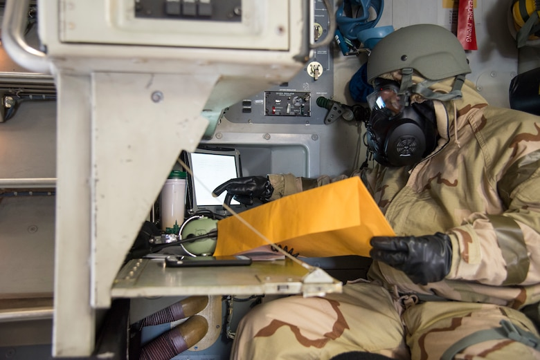 Tech. Sgt. Ryan Page, 3rd Airlift Squadron C-17 Globemaster III loadmaster, runs pre-flight checks while wearing Mission Oriented Protective Posture gear during exercise Vengeant Eagle 2.0 on July 26, 2018, at Dover Air Force Base, Del. This small-scale readiness exercise was designed to test chemical, biological, radiological, and nuclear hazard defensive measures. (U.S. Air Force photo by Tech. Sgt. Laura Beckley)