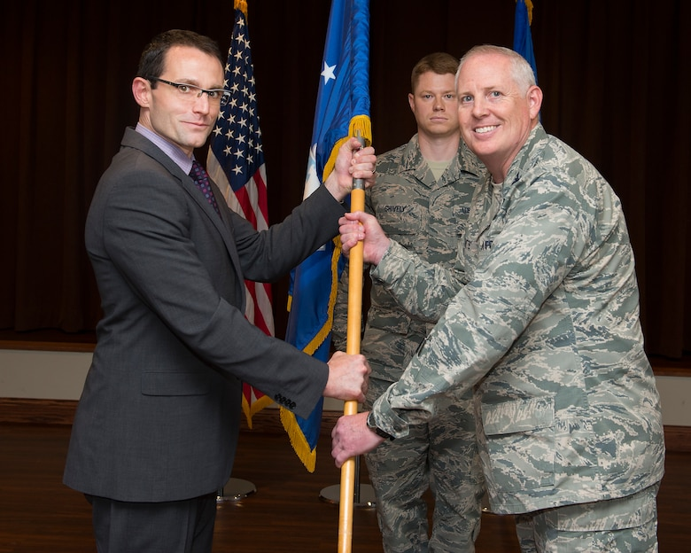 Col. Dale White accepts the guidon from Dr. William Roper, Assistant Secretary of the Air Force for Acquisition, Technology and Logistics, July 26, 2018, as he assumes leadership of the Air Force Life Cycle Management Center's Intelligence, Surveillance, Reconnaissance and Special Operations Forces Directorate during a ceremony in the Wright-Patterson Air Force Base, Ohio club, as Senior Master Sgt. Michael J. Shively looks on. (U.S. Air Force photo by R.J. Oriez)