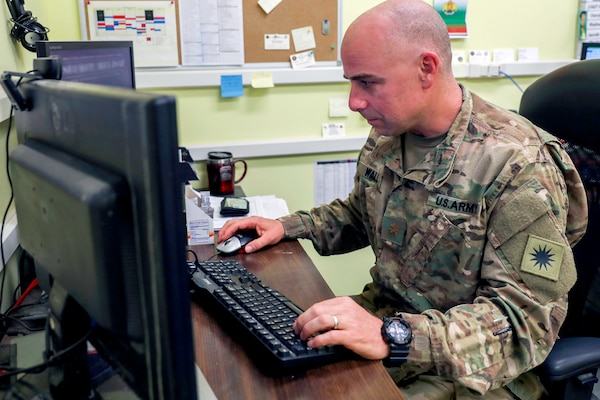 Army Maj. Nathan Wall, of the California Army National Guard's 40th Infantry Division and the deputy logistics officer for Train, Advice and Assist Command-South in Afghanistan, checks email in his office in Kandahar Airfield, Afghanistan. While Wall may be known overseas for working in logistics, back home in Loma Linda, California, he is known as Dr. Wall and teaches a molecular genetics and biochemistry at Loma Linda University School of Medicine.