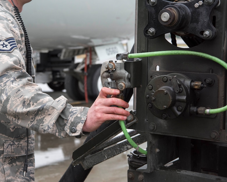 U.S. Air Force Staff Sgt. Matthew Kennedy, a 962nd Aircraft Maintenance Unit E-3 Sentry crew chief, reels in a fuel hose after refueling an E-3 Sentry at Joint Base Elmendorf-Richardson, Alaska, July 25, 2018. Kennedy is responsible for service and repair on everything coming back from daily inspections, to include things like oil, hydraulics and fueling the jet.