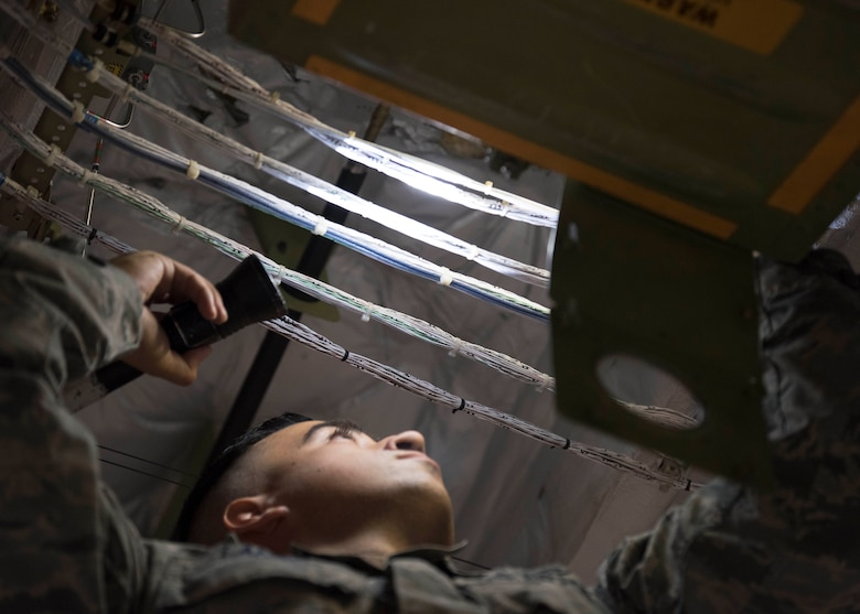 U.S. Air Force Staff Sgt. Caleb Langel, a 517th Aircraft Maintenance Unit C-17 Globemaster III dedicated crew chief, inspects a life raft pressure gauge at Joint Base Elmendorf-Richardson, Alaska, July 26, 2018. Langel is responsible for service and repairs on everything coming back from daily inspections, including making sure the life raft pressure gauge meets specifications to fully inflate if needed.