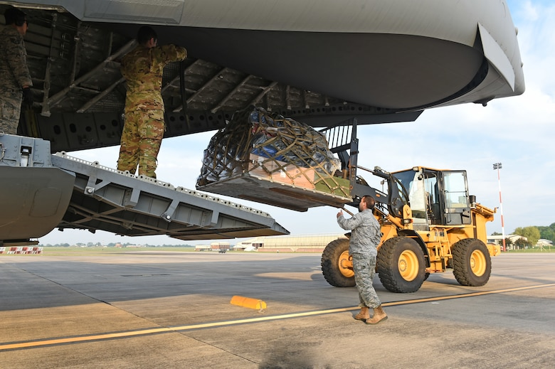 U.S. Air Force Airmen assigned to Air Mobility Command and U.S. Air Forces Europe and Air Forces Africa Command, unload cargo at RAF Fairford, U.K., from a C-17 Globemaster III assigned to Travis AFB, California, May 22, 2018. The C-17 carried approximately 60 Airmen and pallets of cargo in support of Dyess Air Force Base's 345th Expeditionary Bomb Squadron's assurance and deterrence missions in Europe. (U.S. Air Force photo by Senior Airman Emily Copeland)