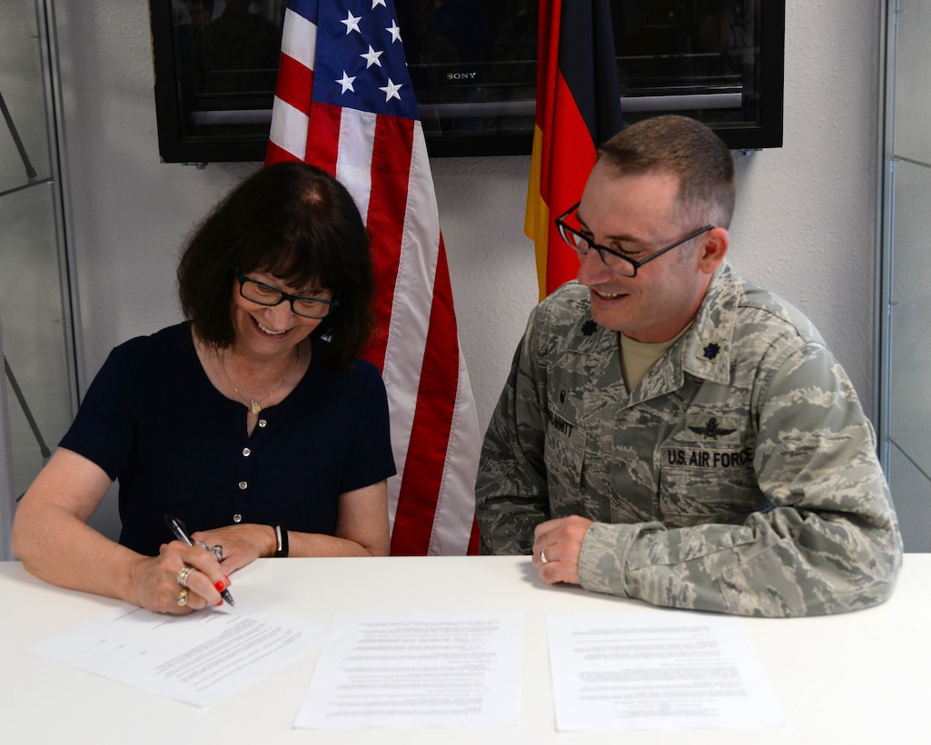 U.S. Air Force Lt. Col. Steven Brummitt, 86th Communications Squadron commander and Sarah Dorosky, 86th Mission Support Group School Liaison Officer sign an Adopt-a-School Partnership Memorandum of Understanding on Ramstein Air Base, Germany, May 31, 2018.