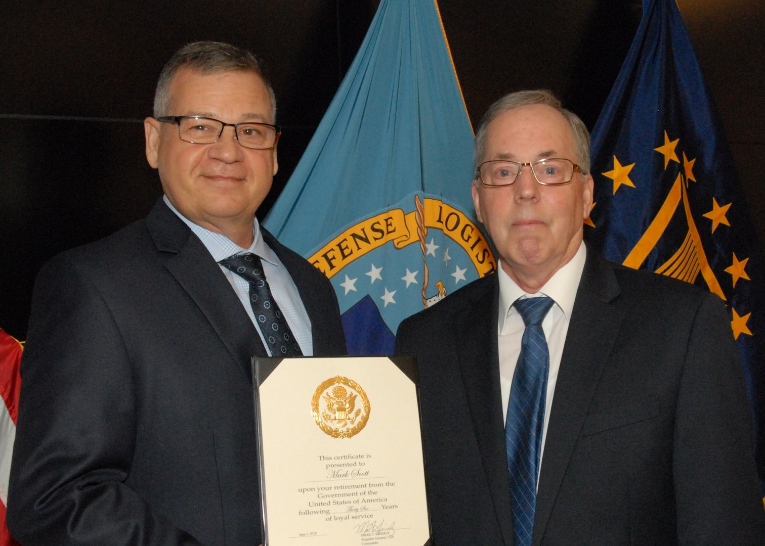 Mark Scott (right), DLA Troop Support Construction and Equipment integrated support team chief, poses for a photo with Troop Support Deputy Commander Richard Ellis (left) during a retirement ceremony May 31 in Philadelphia.