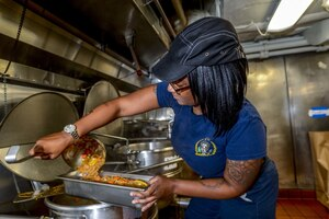 Navy cook prepares a meal.