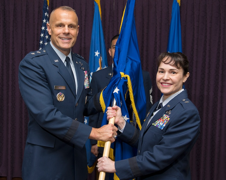 Brig. Gen. Alice W. Treviño accepts the Air Force Installation Contracting Agency flag from Maj. Gen. Bradley D. Spacy, Air Force Installation and Mission Support Center commander, as she becomes the AFICA commander May 23, 2018, during a change of command ceremony in the Wright-Patterson Air Force Base, Ohio, Club.