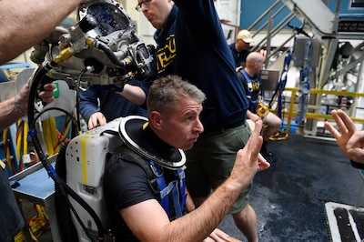 A Navy diver gives the OK sign following his dive using the Office of Naval Research TechSolutions-sponsored MK29 Mixed Gas Rebreather system developed at the Naval Surface Warfare Center Panama City Division, Fla.