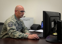 Master Sgt. Justin Koch, 99th Comptroller Squadron first sergeant, checks his email in his office at Nellis Air Force Base, Nevada, May 9, 2018. First shirts can be contacted by calling their first sergeant phone, emailing them or taking a visit to their offices. (U.S. Air Force photo by Airman Bailee A. Darbasie)