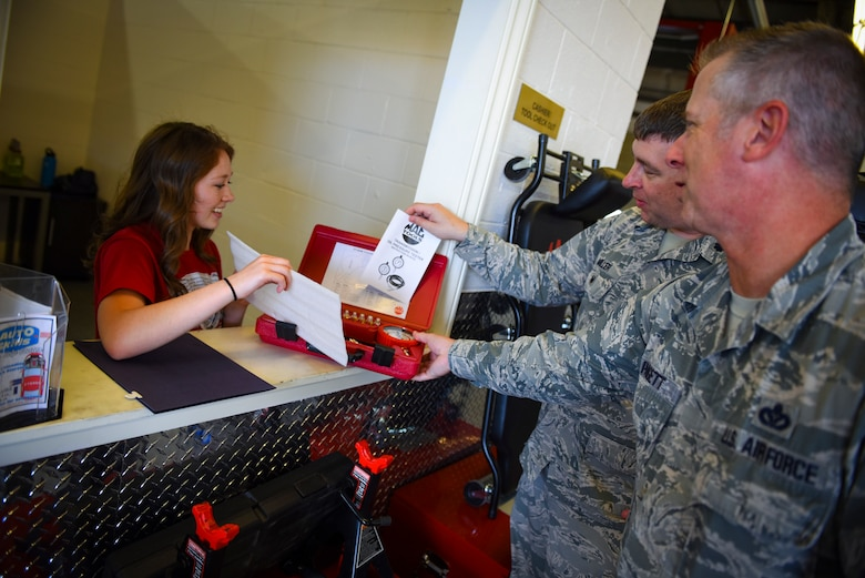 Kearsten Drown, 99th Force Support Squadron Auto Hobby Shop cashier, hands a set of gauges to Lt. Col. Paul Miller, 99th Mission Support Group deputy commander, and Chief Master Sgt. Rob Padgett, 99 MSG superintendent, at Nellis Air Force Base, Nevada, May 31, 2018. The renovations included purchasing new tools and equipment that customers can check out as well as a complete makeover inside the shop to provide a cleaner, climate-controlled area. (U.S. Air Force photo by Airman 1st Class Andrew D. Sarver)