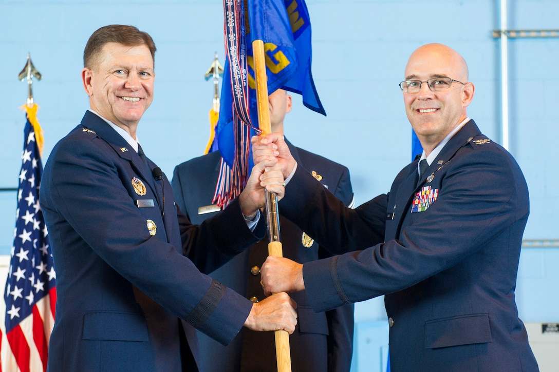 Brig. Gen. Wayne Monteith, commander of the 45th Space Wing presents Col. Steven Lang, commander of the 45th Launch Group and the 45th Operations Group with the 45th OG guidon, June 1, 2018 at Cape Canaveral Air Force Station, Fla. Lang assumed command from Col. Burton Catledge, and took on the role of the 45th LCG and the 45th OG commander. (U.S. Air Force photo by Phil Sunkel)