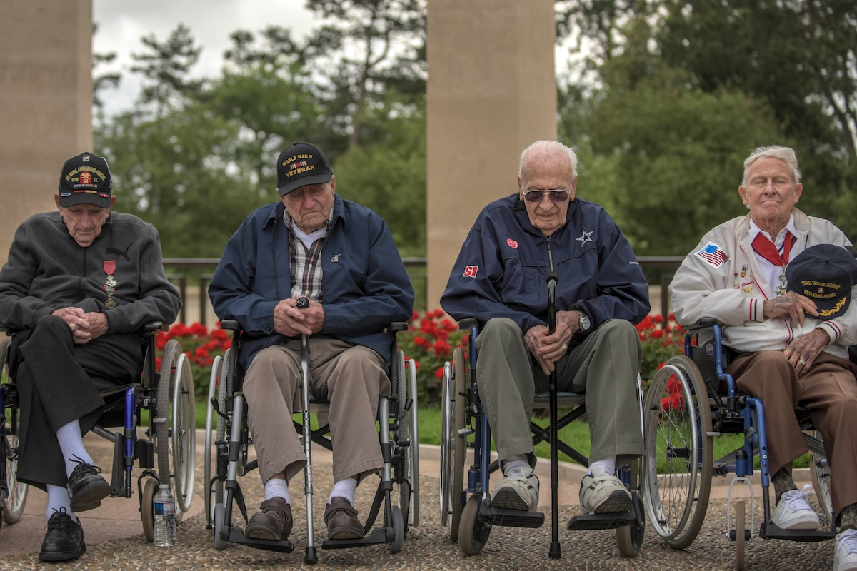 Four veterans sit in a row in wheelchairs at a memorial.