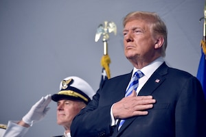 The president places his hand over his heart while a Coast Guard admiral salutes.
