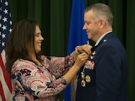 Leslie Butikofer fastens the retirement pin on Brig. Gen. Mitchel Butikofer's, Air Forces Cyber vice commander, lapel during his retirement ceremony at Joint Base San Antonio-Lackland, Texas, June 1, 2018. Butikofer retired after 29 years of service. (U.S. Air Force photo by Tech. Sgt. R.J. Biermann)