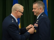 Maj. Gen. Chris Weggeman, Air Forces Cyber commander, pins the Distinguished Service Medal on Brig. Gen. Mitchel Butikofer's, AFCYBER vice commander, lapel at Joint Base San Antonio-Lackland, Texas, June 1, 2018. Butikofer retired after 29 years of service. (U.S. Air Force photo by Tech. Sgt. R.J. Biermann)