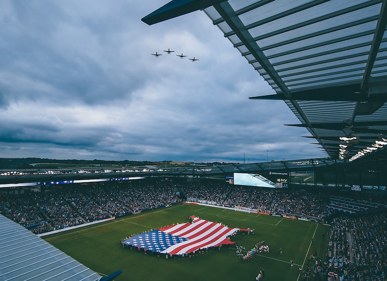 Four A-10 Thunderbolt II attack aircraft fly over Children's Mercy Park as a flag is unfurled on the field below in August 2017.