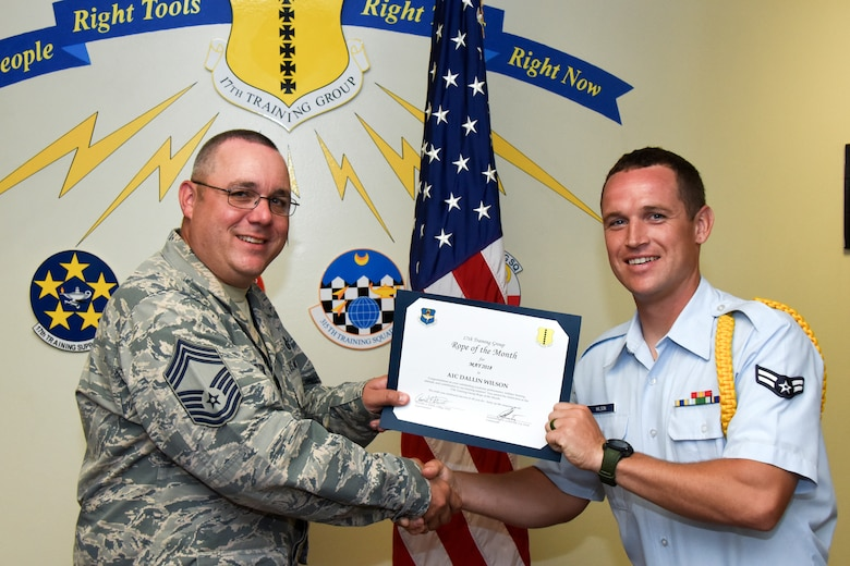 U.S. Air Force Chief Master Sgt. Daniel Stein, 17th Training Group superintendent, presents the 17th TRG Rope of the Month award to Airman 1st Class Dallin Wilson, 312th Training Squadron trainee, at Brandenburg Hall on Goodfellow Air Force Base, Texas, June 1, 2018. The 312th TRS's mission is to provide Department of Defense and international customers with mission ready fire protection and special instruments graduates and provide mission support for the Air Force Technical Applications Center. (U.S. Air Force photo by Airman 1st Class Zachary Chapman/Released)